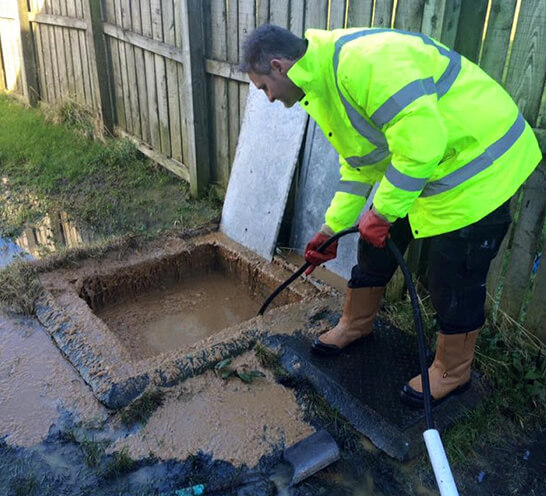 one of our blocked drain experts Jim unblocking an external drain pipe
